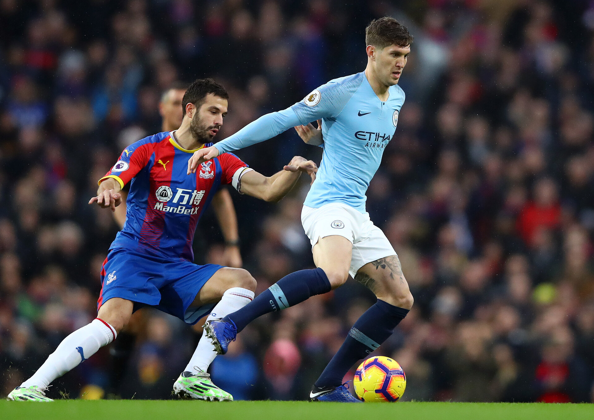 MANCHESTER, ENGLAND - DECEMBER 22: John Stones of Manchester City is challenged by Luka Milivojevic of Crystal Palace during the Premier League match between Manchester City and Crystal Palace at Etihad Stadium on December 22, 2018 in Manchester, United Kingdom.  (Photo by Clive Brunskill/Getty Images)