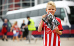 SOUTHAMPTON, ENGLAND - AUGUST 03: A young Southampton fan stops for a photo with the latest match day magazine ahead of the Pre-Season Friendly match between Southampton FC and FC Köln pictured at St. Mary's Stadium on August 03, 2019 in Southampton, England. (Photo by James Bridle - Southampton FC/Southampton FC via Getty Images)