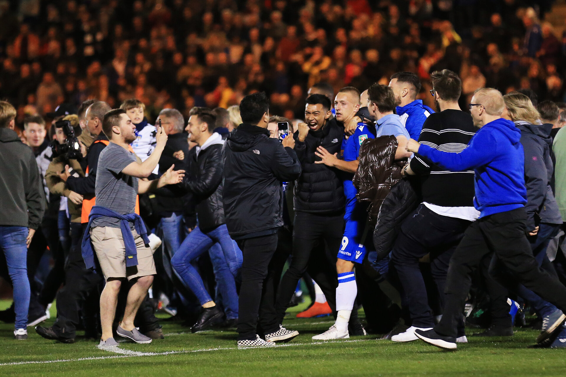 COLCHESTER, ENGLAND - SEPTEMBER 24: Luke Norris of Colchester United is surrounded by fans after they invade the pitch following Colchester United victory in the penalty shoot during the Carabao Cup Third Round match between Colchester United and Tottenham Hotspur at JobServe Community Stadium on September 24, 2019 in Colchester, England. (Photo by Stephen Pond/Getty Images)