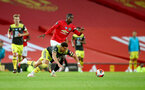 MANCHESTER, ENGLAND - JULY 13: Ché Adams(L) of Southampton is fouled by Paul Pogba of Manchester United during the Premier League match between Manchester United and Southampton FC at Old Trafford on July 13, 2020 in Manchester, United Kingdom. Football Stadiums around Europe remain empty due to the Coronavirus Pandemic as Government social distancing laws prohibit fans inside venues resulting in all fixtures being played behind closed doors. (Photo by Matt Watson/Southampton FC via Getty Images)
