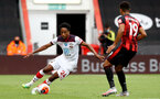 BOURNEMOUTH, ENGLAND - JULY 19: Kyle Walker-Peters (L) of southampton and Junior Stanislas (R) of bournemouth during the Premier League match between AFC Bournemouth and Southampton FC at Vitality Stadium on July 19, 2020 in Bournemouth, United Kingdom. Football Stadiums around Europe remain empty due to the Coronavirus Pandemic as Government social distancing laws prohibit fans inside venues resulting in all fixtures being played behind closed doors. (Photo by Matt Watson/Southampton FC via Getty Images)