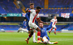 LONDON, ENGLAND - OCTOBER 17:  Kyle Walker-Peters (center) of Southampton being tackled by Ben Chilwell (R) and Mason Mount (L) of Chelsea during the Premier League match between Chelsea and Southampton at Stamford Bridge on October 17, 2020 in London, United Kingdom. Sporting stadiums around the UK remain under strict restrictions due to the Coronavirus Pandemic as Government social distancing laws prohibit fans inside venues resulting in games being played behind closed doors. (Photo by Matt Watson/Southampton FC via Getty Images)