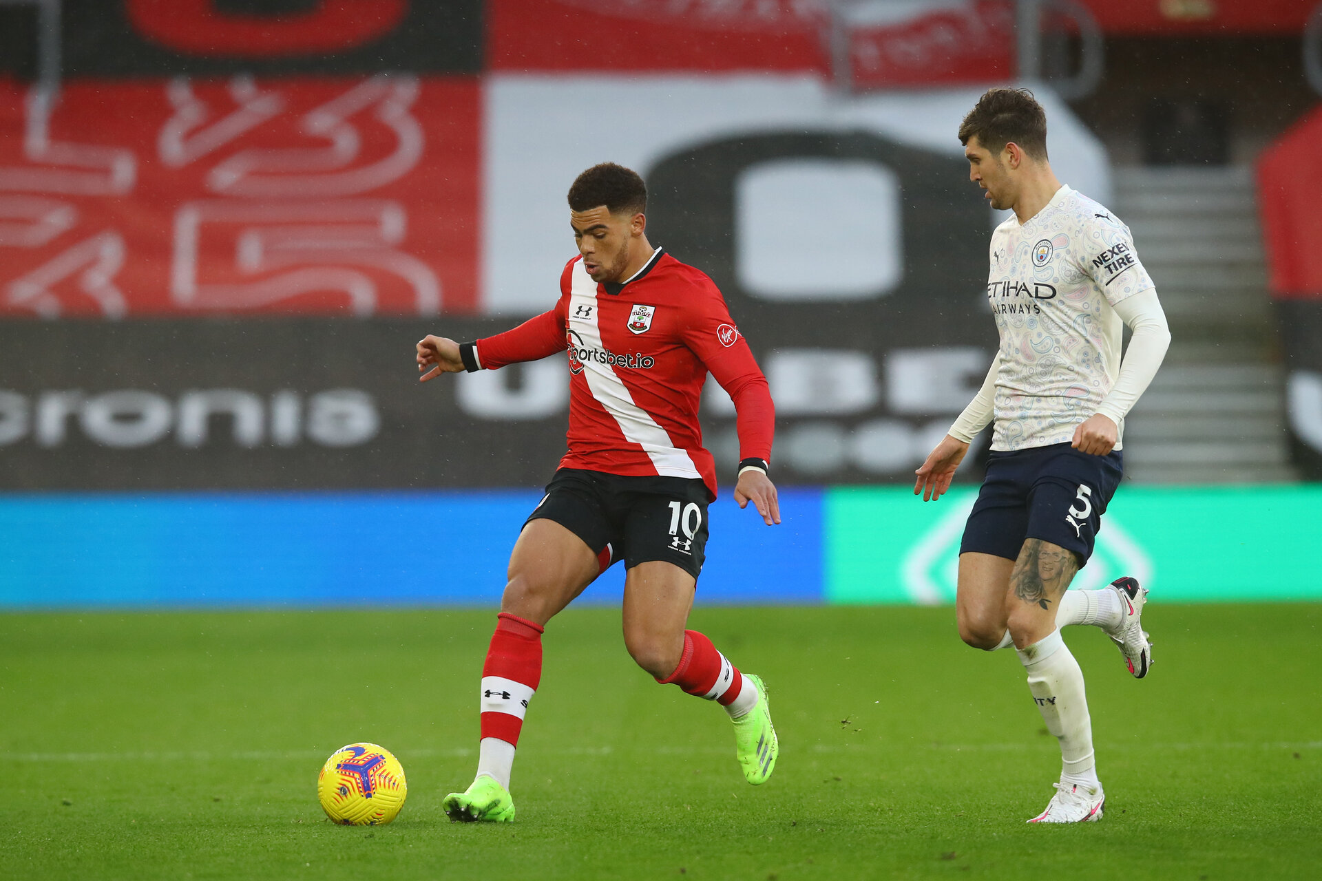 SOUTHAMPTON, ENGLAND - DECEMBER 19: Ché Adams (L) of Southampton and John Stones (R) Manchester City during the Premier League match between Southampton and Manchester City at St Mary's Stadium on December 19, 2020 in Southampton, England. A limited number of fans (2000) are welcomed back to stadiums to watch elite football across England. This was following easing of restrictions on spectators in tiers one and two areas only. (Photo by Matt Watson/Southampton FC via Getty Images)
