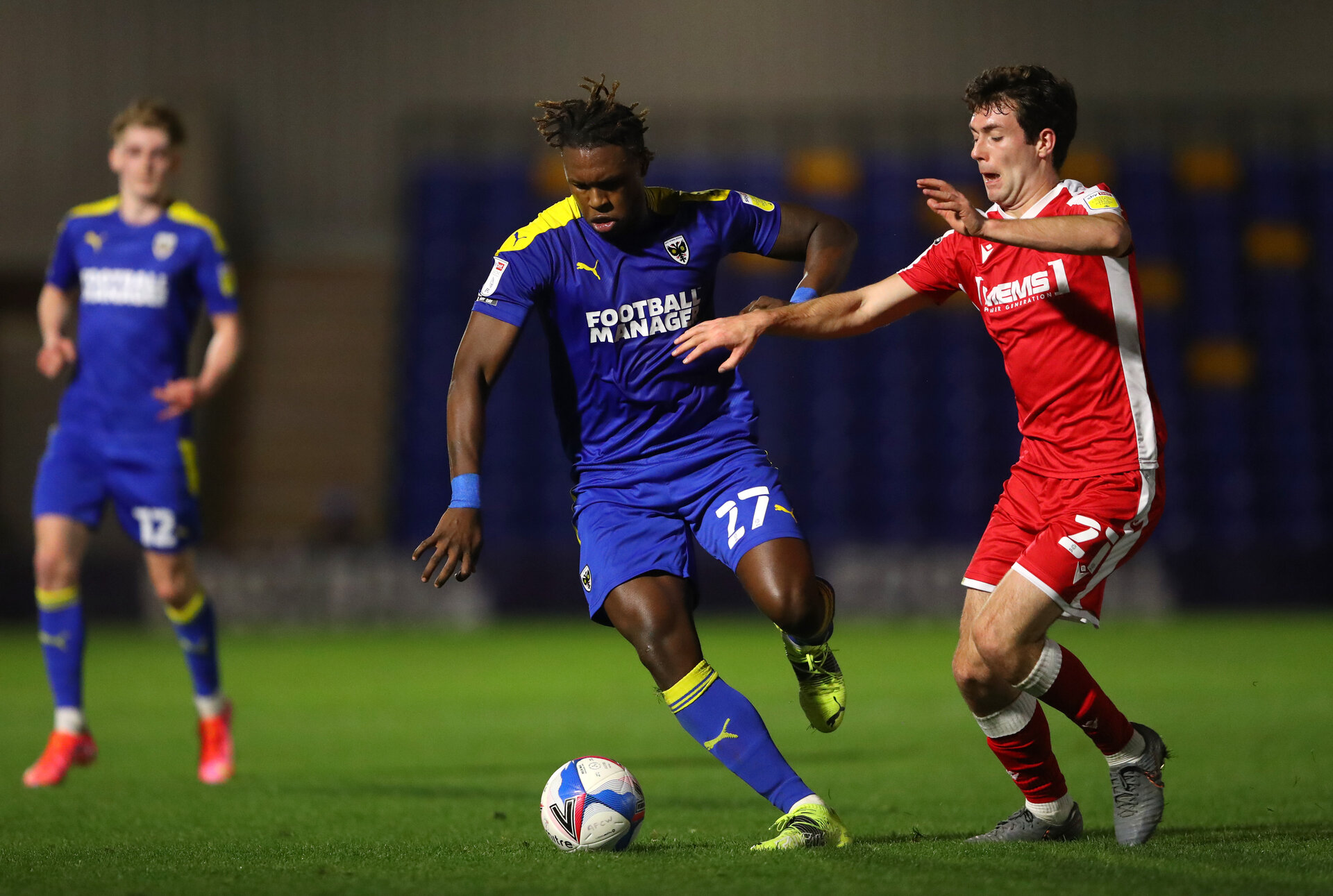 WIMBLEDON, ENGLAND - FEBRUARY 23:  Darnell Johnson of AFC Wimbledon holds off Thomas O'Connor of Gillingham FC during the Sky Bet League One match between AFC Wimbledon and Gillingham at Plough Lane on February 23, 2021 in Wimbledon, England. Sporting stadiums around the UK remain under strict restrictions due to the Coronavirus Pandemic as Government social distancing laws prohibit fans inside venues resulting in games being played behind closed doors. (Photo by Warren Little/Getty Images)