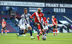 WEST BROMWICH, ENGLAND - APRIL 12: Nathan Redmond(R) of Southampton and Callum Robinson(L) of West Brom during the Premier League match between West Bromwich Albion and Southampton at The Hawthorns on April 12, 2021 in West Bromwich, England. Sporting stadiums around the UK remain under strict restrictions due to the Coronavirus Pandemic as Government social distancing laws prohibit fans inside venues resulting in games being played behind closed doors. (Photo by Matt Watson/Southampton FC via Getty Images)