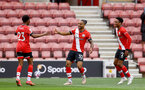 SOUTHAMPTON, ENGLAND - MAY 15: Theo Walcott (center) of Southampton celebrates scoring with Nathan Tella(L) and Kyle Walker-Peters(R) during the Premier League match between Southampton and Fulham at St Mary's Stadium on May 15, 2021 in Southampton, England. Sporting stadiums around the UK remain under strict restrictions due to the Coronavirus Pandemic as Government social distancing laws prohibit fans inside venues resulting in games being played behind closed doors.  (Photo by Matt Watson/Southampton FC via Getty Images)